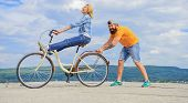 Learn Cycling With Support. Cycling Technique. Woman Rides Bicycle Sky Background. Man Helps Keep Ba poster