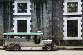 image of luzon  - local built jeepney filipino public transport parked outside derelict building in intramuros manila philippines - JPG