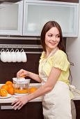 Woman Making Orange Juice In Kitchen