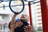 foto of snatch  - Child is snatching a gym ring at the outdoor playground - JPG