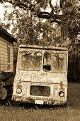 stock photo of ice-cream truck  - Sepia toned courier or maybe ice cream truck abandoned and covered in moss and lichens