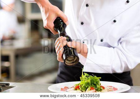 Постер, плакат: Шеф повар в гостинице или ресторане кухня приготовления пищи только руки видно он приправа блюда, холст на подрамнике