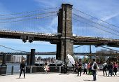 Photographer with the crew shooting young model under Brooklyn Bridge