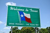 image of texas state flag  - A Welcome to Texas road sign set against a light blue background showing the state flag - JPG