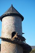 stock photo of billy goat  - Billy goat on a goat tower against a blue sky - JPG