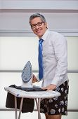 Businessman smiling while ironing pants