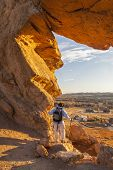stock photo of backbone  - male hiker looking through a keyhole in Devil - JPG