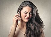 picture of noise pollution  - portrait of annoyed girl on the phone - JPG