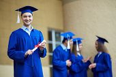 Friendly students in graduation gowns interacting with confident guy in front
