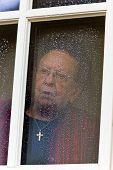 aus einem Fenster sucht versonnen Senior traurig