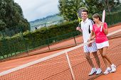 Couple of tennis players at the court and holding rackets