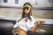 Beautiful woman posing glamor style beside aircraft plane