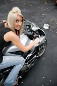 image of crotch-rocket  - A young blonde woman poses on her motorcycle - JPG
