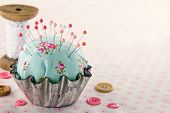 picture of sewing  - Green handmade floral pincushion in an old metal cupcake with buttons and spools of thread and lace sewing concept background - JPG