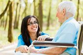 stock photo of retirement age  - Kind nurse laughing with elderly patient in wheelchair - JPG