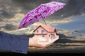 Hand holding a house with an umbrella of protection