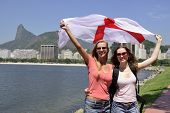 Couple of female sport fans holding the England flag in Rio de Janeiro with Christ the Redeemer in