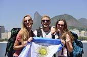Group of sport fans friends traveling at Rio de Janeiro holding Argentinian flag, with Christ Redeem
