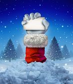 stock photo of avalanche  - Santa Claus winter sign as a hand holding a blank card emerging out of a pile of avalanche snow in a cold pine forest scene as a funny Christmas symbol and joyous seasonal holiday celebration message - JPG