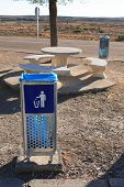 stock photo of dustbin  - Dustbin and stone tables for picnic near road - JPG
