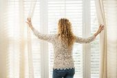 pic of lace-curtain  - Woman looking out big bright window with curtains and blinds - JPG