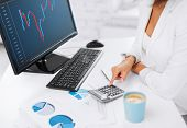business, office and money concept - woman hand with calculator, papers, monitor and forex chart on