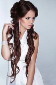 Beautiful Woman With Long Brown Hair Wearing In White Dress Isolated On Grey Background. Jewelry And