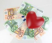 Love for money concept. Heart on European currency isolated on white