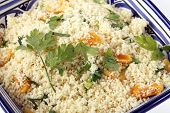 A colourful Tunisian blue and white bowl with couscous mixed with chopped dried apricots and fresh parsley
