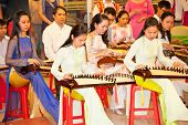 HO CHI MINH, VIETNAM- NOV 16, 2013: Unidentified Vietnamese musicians performing music on Zither, tr