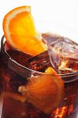 Glass of cold cola drink with ice and orange, shot over white background