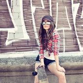 Portrait of beautiful teen girl standing on skateboard over wall with abstract graffiti art. Urban outdoors, teenager's lifestyle. Toned.