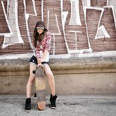 Portrait of beautiful teen girl standing on skateboard over wall with abstract graffiti art. Urban o