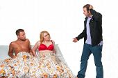 stock photo of threesome  - Man holding hand on his head looking surprised when he finds his wife in red lingerie lying in bed with a tanned naked man - JPG