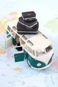 foto of camper-van  - Camper van with a stack of suitcases on a map - JPG