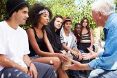 stock photo of gang  - Senior Man Talking With Gang Of Young People - JPG