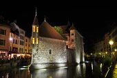 ANNECY, FRANCE - SEPTEMBER 16, 2012: Summer night in the charming medieval town. Castle illuminated by spotlights and is beautifully reflected in the dark water.