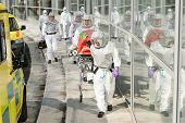 foto of stretcher  - Biohazard team with stretcher wear protective uniform walking outside building - JPG