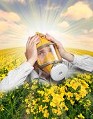 Unhappy man in protection mask in a rape field. Allergy concept.