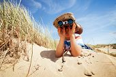 Little boy searching with binoculars at the beach dressed as explorer concept for nature, discovery,