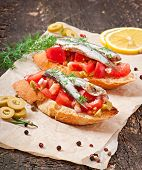 Crostini with anchovies, olives and tomatoes
