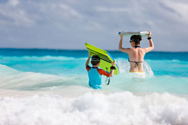 stock photo of boogie board  - Mother and son running towards ocean with boogie boards - JPG