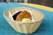 Slices of bread and butter in a basket on table