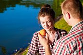 Young girl eating peach or nectarine fruit smiling