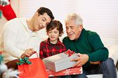 Men and child in three generations celebrating christmas with gifts