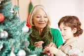 Grandchild and grandmother decorating together the christmas tree