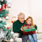 Granddad giving gift to granddaughter at christmas