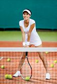 Pretty sportswoman at the tennis court with racquet. Training time