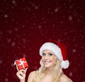 Pretty woman in Christmas cap hands present wrapped with red paper, isolated on purple snowy background
