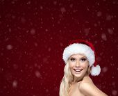 Beautiful woman in Christmas cap, isolated on purple